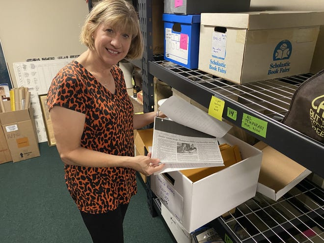 """Kristin Greenberg, who took over as executive director of the Upper Arlington Historical Society Sept. 16, displays documents that provide history of some of Upper Arlington's oldest homes. The information was collected as part of the historical society's """"Homes of History"""" tour that was held in August."""