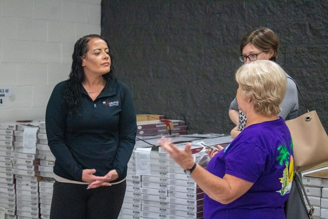 Kaytee Miller talks to two customers about flooring options at National Design Mart's new Wooster location. A grand opening celebration is planned for Saturday, Oct. 2.