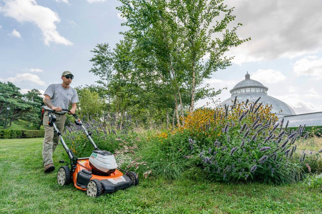 Tyler Campbell mows the grounds in front of the Enid A. Haupt Conservatory at the New York Botanical Garden in the Bronx borough of New York.