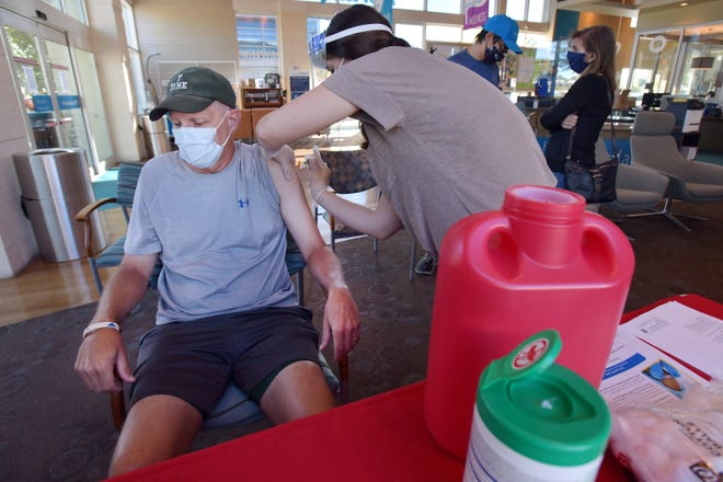 Tom Ashton gets his flu shot Wednesday morning. The Ashton Family from Jacksonville's Baymeadows area all came to the Florida Blue Center at the St. Johns Town Center to get their shots.
