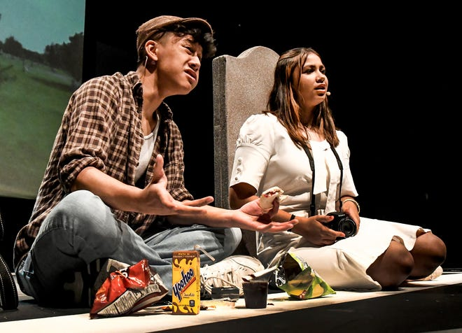 """Earl the gravedigger, played by Bryant Detvongsa, left, talks with the ghost of Suzanne the photographer, portrayed by Katrina Almaguer, at her gravesite as he eats lunch Tuesday during a rehearsal scene from Garden City High School's production of """"Kodachrome"""". Performances begin Friday in the school's auditorium."""