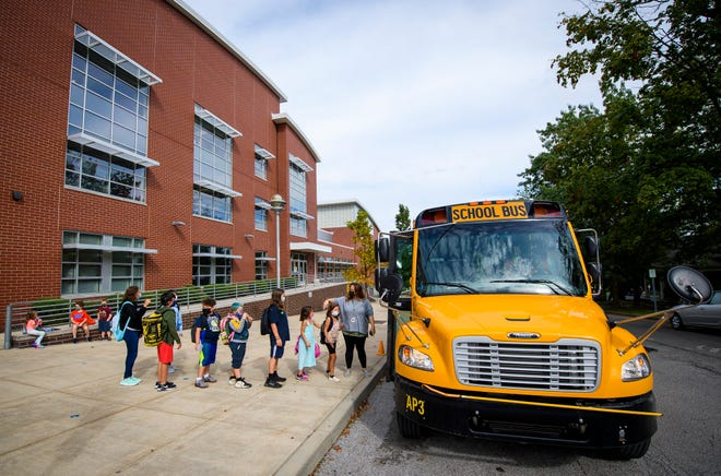 Fairview Elementary students line up to get on a bus as Jen Maksimov watches on Sept. 21.