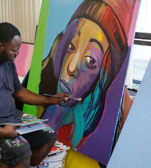 Chicago artist Damon Lamar Reed paints a portrait of Alexis Scott, a Peoria woman who has been missing since Sept. 23, 2017. The portrait is one of about a dozen that highlight missing women in Illinois.