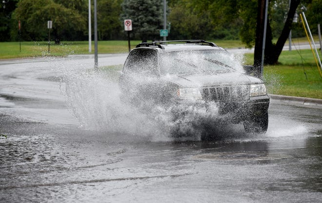 An SUV plows through the flooded intersection of Winchester and Front Streets in the City of Monroe Wednesday morning.