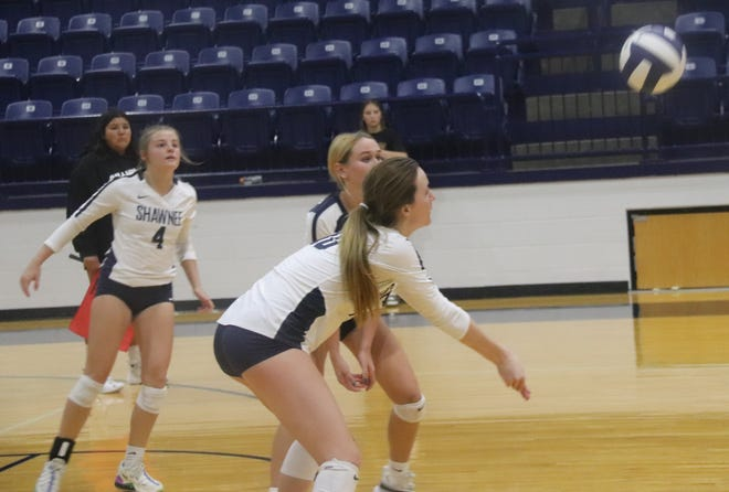 Shawnee's Kylie Mikish (10) prepares to go for the dig as teammates Madison Crowell (4) and Isabelle Conley (5) look on Monday during the Lady Wolves' match against Duncan.