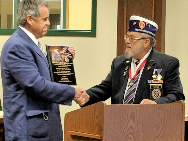 Mayor Paul Adamson accepts the Purple Heart Plaque from Larry Emery of the Military Order of the Purple Heart #699
