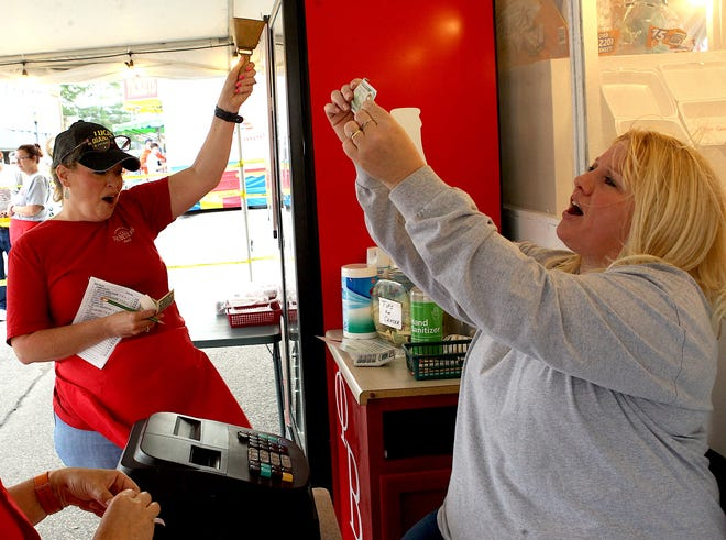 Kelli Lucas rings the bell and Amy Brothers cheers as another sale is made at the Persimmon Festival Phi Beta Psi sorority food stand. The bell is rung every time a tip is placed in the tip jar. All proceeds from the tip jar go to help Lawrence County cancer patients.