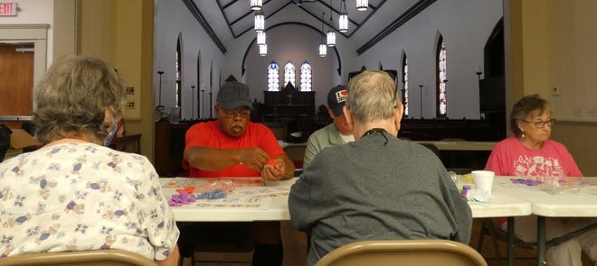 A group of seniors plays bingo at Galion History Center's Historic Grace Church last week. The activity was offered by the Crawford County Council on Aging.