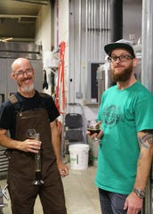Brewmaster Rick Vickers (left) and Mechanical Brewery owner James Griffin enjoy an early taste of Momentum, an award-winning mild English ale, in the brewery.