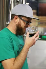 Mechanical Brewing owner James Griffin tests the aroma of a pour of Momentum at the Cherry Hill brewery. The mild English ale took home a gold medal from Great American Beer Awards earlier this month.