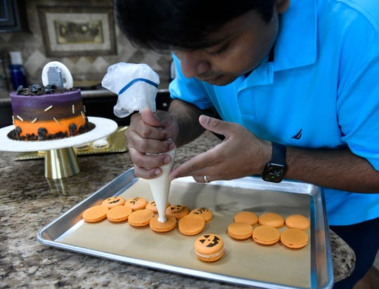 Anirudh Mamtora prepares Halloween macarons as jack-o'-lanterns and a mummy in his Cherry Hill kitchen.