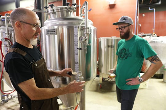 Head brewer Rick Vickers (left) and brewery owner James Griffin work together at Mechanical Brewery in Cherry Hill.