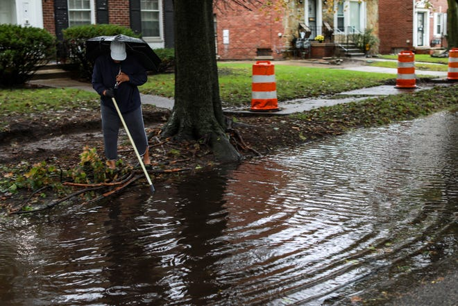 A Detroit resident clears debris from a storm drain to stop flooding in front of her home in the Green Acres neighborhood on Sept. 22, 2021.