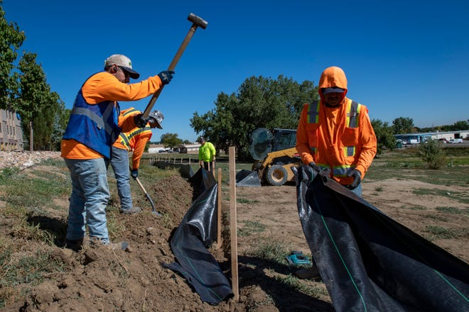 Metco Landscape employee Damian Granados, left, and his co-workers install a slit fence, Wednesday, Sept. 22, 2021, at a site that could eventually be home to 90 apartments known as Mars Landing in Fort Collins.
