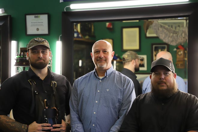 Steve Walski (left), Chris Martino (center), and Rickey Bright (right) pose for a photo inside Legionnaires Barbershop. All three men are veterans of the U.S. Military.