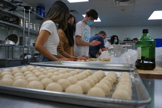 Students from the Carlsbad High School culinary program make break rolls for their Meals To Go program.