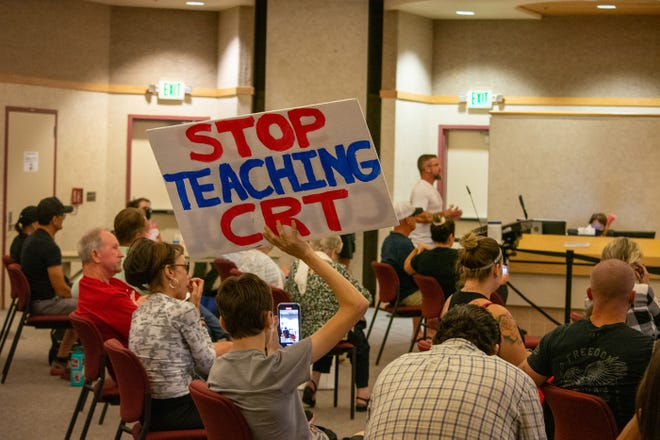 """Student Chase Coughlin holds a sign to """"Stop Teaching CRT,"""" or critical race theory, at the DSUSD board meeting in La Quinta, Calif., on Sept. 21, 2021."""