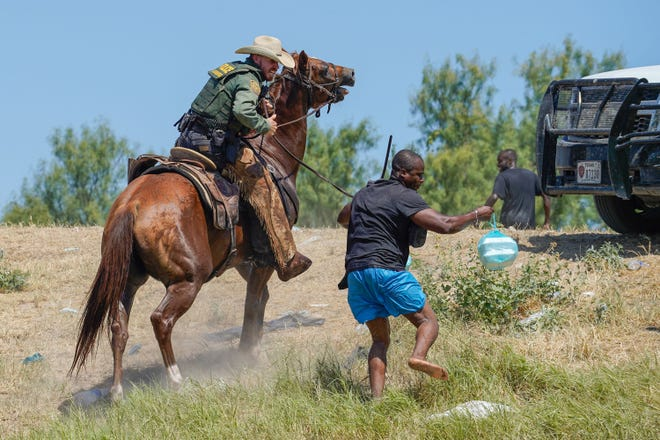 A U.S. Border Patrol agent on horseback uses the reins to try and stop a Haitian migrant from entering an encampment on the banks of the Rio Grande near the Acuna Del Rio International Bridge in Del Rio, Texas on Sunday, September 19, 2021. (Paul Ratje/AFP/Getty Images/TNS)