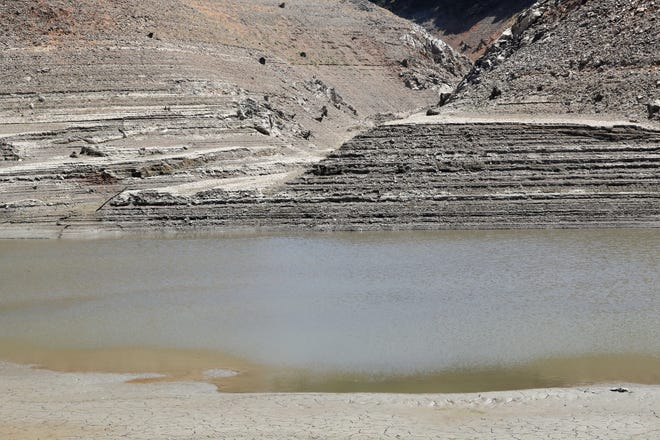 Like rings in a bathtub, Lake Shasta's dropping water levels leave their mark in August 2021.