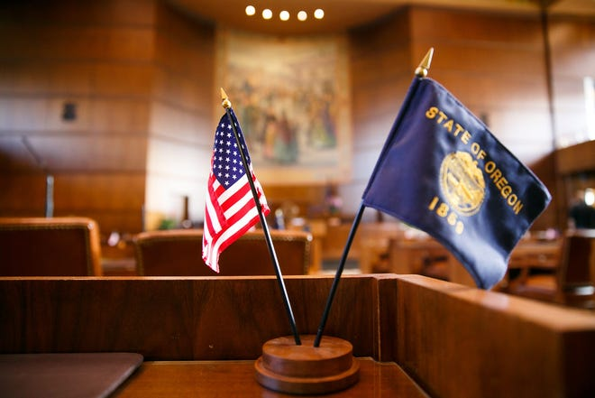 An American flag and the flag of Oregon on a legislator's desk in the Senate Chamber at the Oregon State Capitol.
