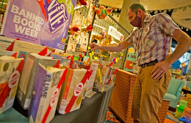 Rob Honegger looks over a display about banned books in the children's section of the Stephens Central Library on Tuesday, Sept. 21, 2021.