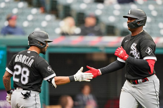 Chicago White Sox's Eloy Jimenez, right, celebrates with Leury Garcia after Jimenez hit a solo home run in the second inning in the first baseball game of a doubleheader against Cleveland, Thursday, Sept. 23, 2021, in Cleveland. (AP Photo/Tony Dejak)