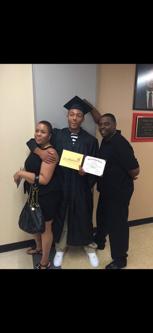 """Alexander """"AJ"""" Beasley, center, with his mother, Keesha Wilson-Law, and his stepfather, Damione Law."""