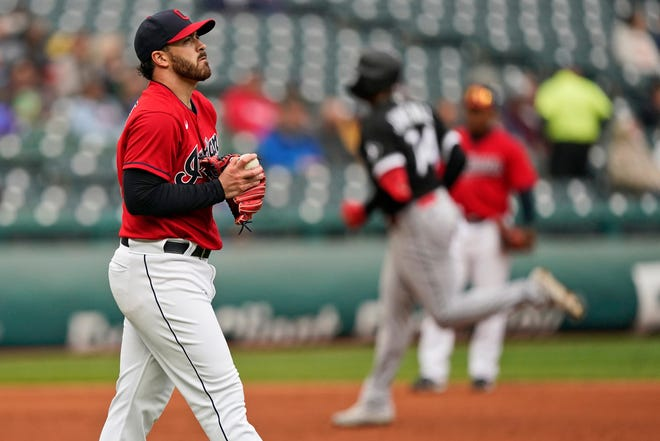 Cleveland starting pitcher Aaron Civale, left, waits for Chicago White Sox's Eloy Jimenez to run the bases after Jimenez hit a solo home run in the second inning in the first baseball game of a doubleheader, Thursday, Sept. 23, 2021, in Cleveland. (AP Photo/Tony Dejak)