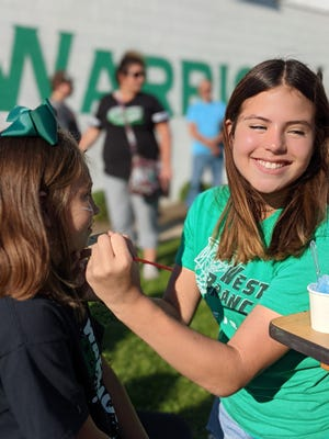 Girls basketball player Presley Egli smiles while applying face-paint to a young Warrior student during the Sept. 10 Back-2-School Bash.