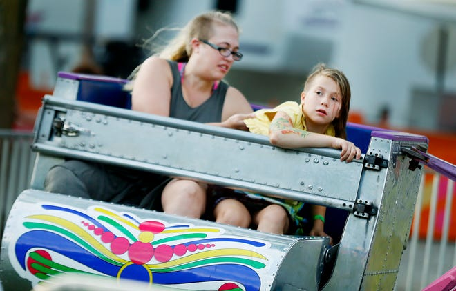 Chelsie Troyer, left, and daughter Naveyah go on a spinning ride during the 131st Loudonville Street Fair in 2019. This year's Loudonville Street Fair will be Oct. 5-9.