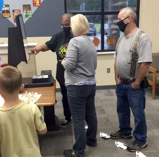 Patrons learn how to use the new self-checkout system at the Crestview Public Library recently.