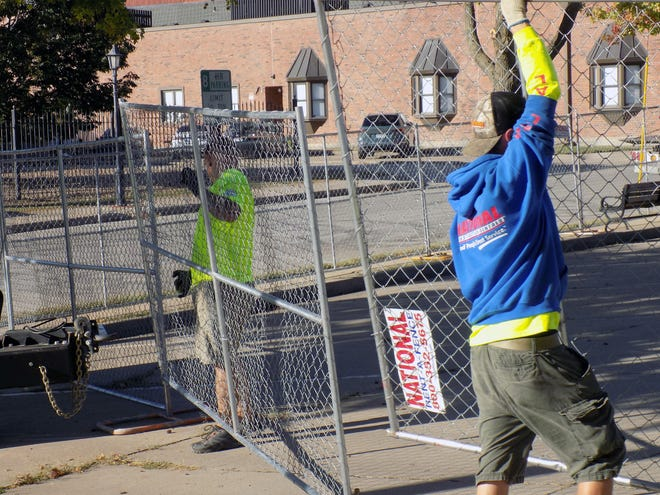 Zack Hoyer and Jonathon Woodrome of National Construction Rentals put up fencing Thursday in downtown Leavenworth in preparation for Camp Leavenworth. The festival will begin today and continue Saturday.