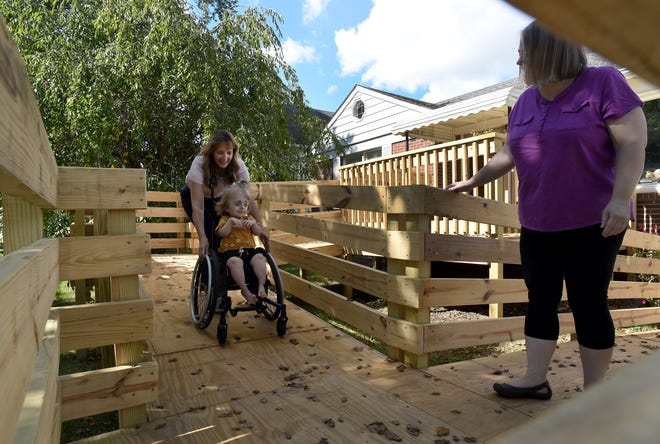 Buffy Ruddy, a physical therapist working with the Monroe County Intermediate School District, helps Aurora Lewis, 6, of Monroe navigate the newly-installed ramp at her home as Nichole Lewis, Aurora's mother, looks on.