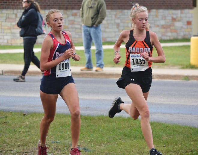 Boyne City's Ava Maginity (left) and Harbor Springs' Maye Burns (right) run during the Bulldog Invite Wednesday, in which Maginity placed first overall and Burns was second.