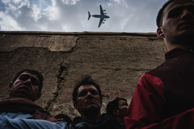 A military transport plane flies over as Afghans mourn family members who died last month in Kabul, Afghanistan.