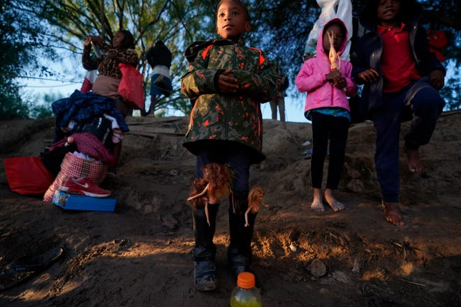 A girl with Barbie dolls stuffed in her boots waits with others to cross the Rio Grande river with their parents as they stand on the southern bank of the Rio Grande river in Ciudad Acuna, Mexico, at dawn Thursday.