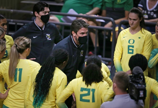 Oregon volleyball coach Matt Ulmer, center, gives his team directions before their match against Oregon State on Sept. 22 at Matthew Knight Arena.