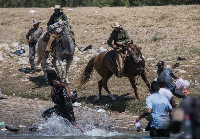 U.S. Customs and Border Protection mounted officers attempt to contain migrants as they cross the Rio Grande from Ciudad Acuña, Mexico, into Del Rio, Texas, Sept. 19, 2021.