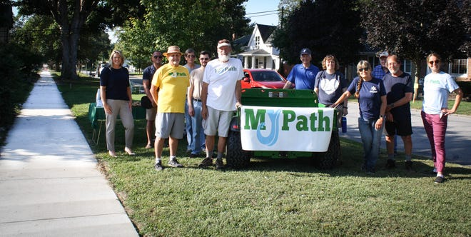 Volunteers and community partners gather to celebrate to celebrate the ribbon cutting for the extension of the sidewalk system as it connects the MyPath Trail System on the south side of Spencer.