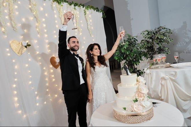 Kristen, à direita, e Basil, à esquerda, brindam a seus convidados em um casamento organizado pela Imperfectly Perfect Wedding and Events.