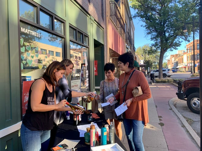 Abby Cogley, left,  and Erica Samson,  of Sun City Tanning Studio pour wine for Penny Stolsmark and Barb Rosebrock at the Wine Walk on Wednesday evening. This event is sponsored by the Aberdeen Downtown Association.