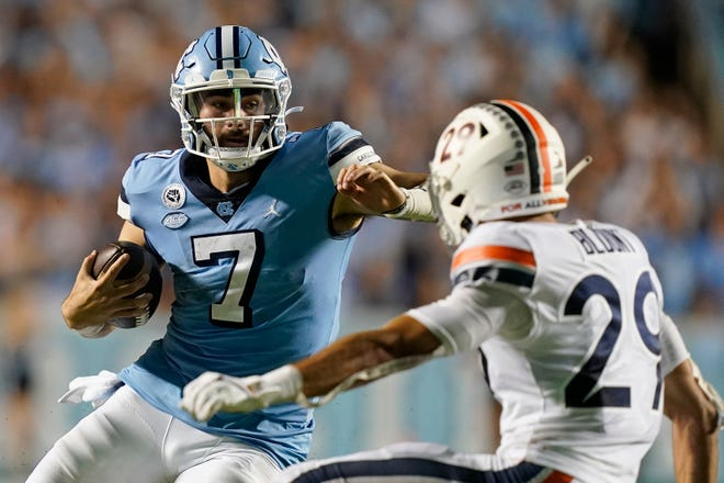 North Carolina quarterback Sam Howell puts a move on Virginia defensive back Joey Blunt, front, during a run in the second half of last week's game.