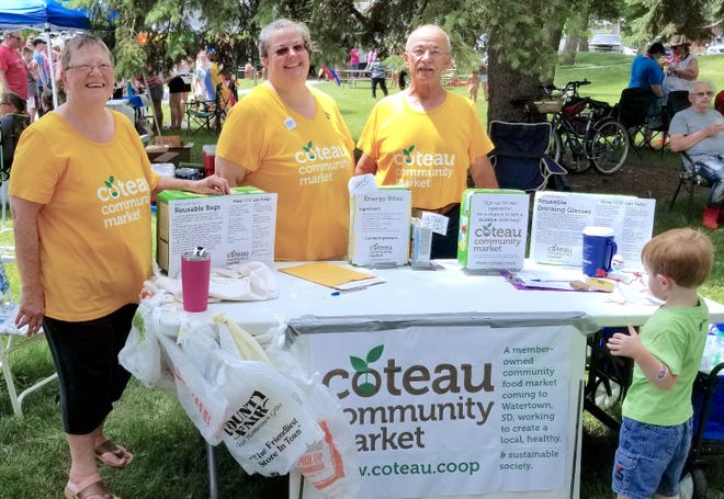 Annie Mullin, center, and her parents Jan and Mike, inform the public about the Coteau Community Market and encourages others to become members during Watertown Love in 2019.
