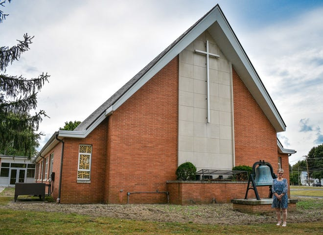 """Clyde First United Methodist Church is on """"Piety Hill"""" at the corner of Maple and Race streets in Clyde. Two hundred years ago, the church's first congregation met in a log cabin at the same location. Standing in front of the church is the Rev. Sheryl Seitz, the church's first female pastor in its two century history."""