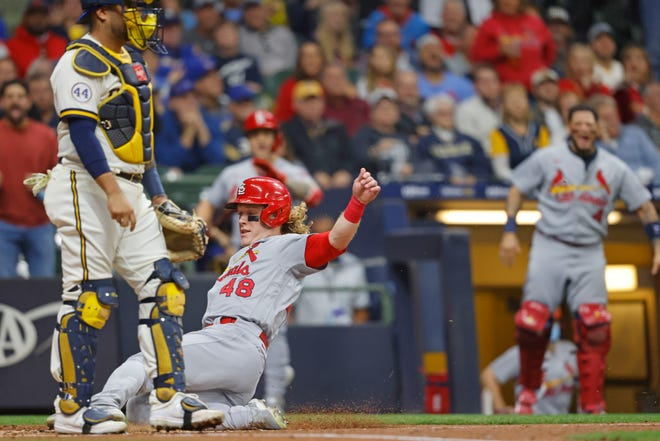 The Cardinals' Harrison Bader scores from second base on sacrifice fly during the second inning against the Brewers on Wednesday night.