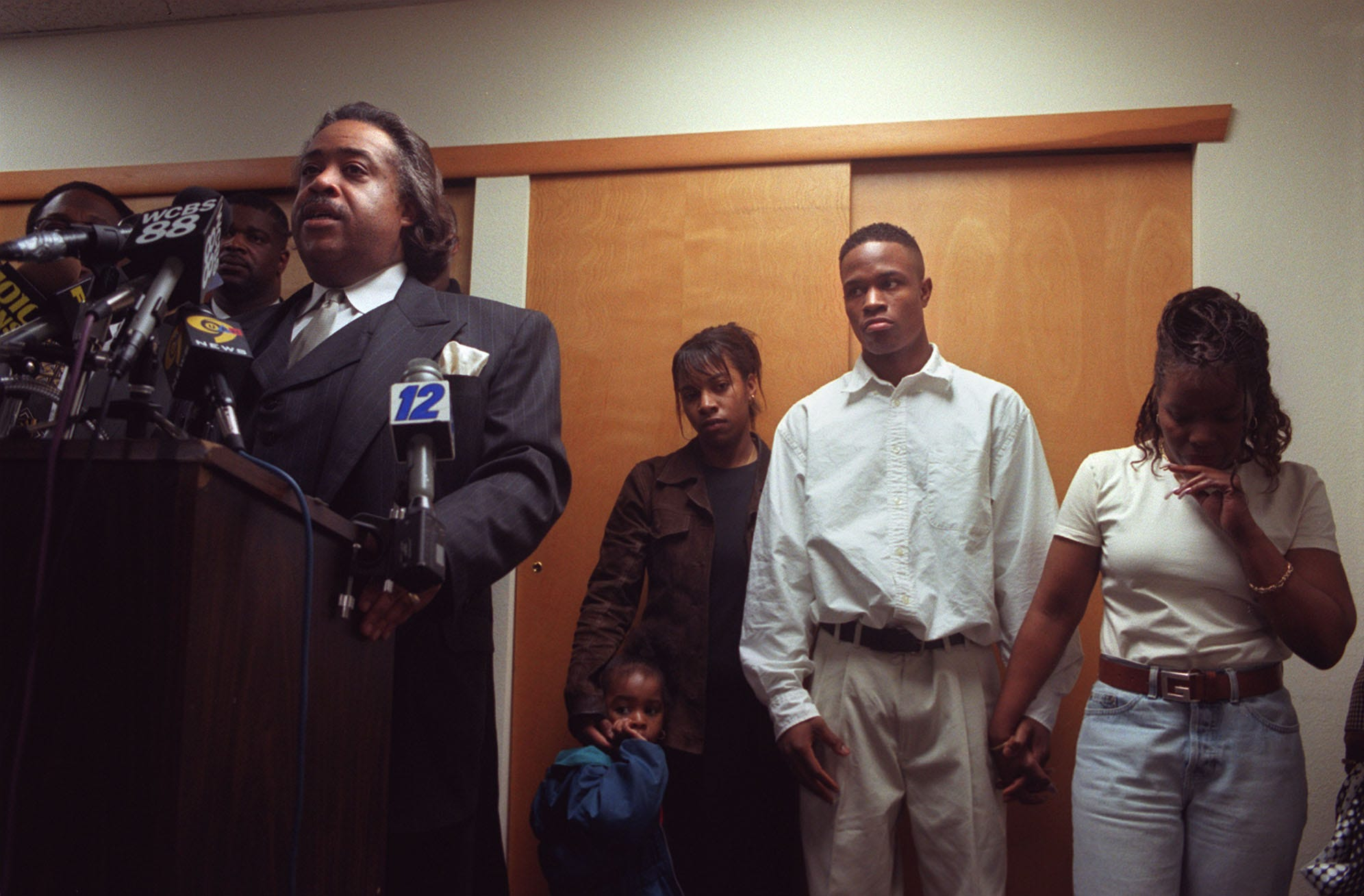 Keshon Lamonte Moore, 22, stands with family at his sides as Rev. Al Sharpton speaks during a press conference at Abyssinian Baptist Church, in Newark, Sunday, April 26, 1998.