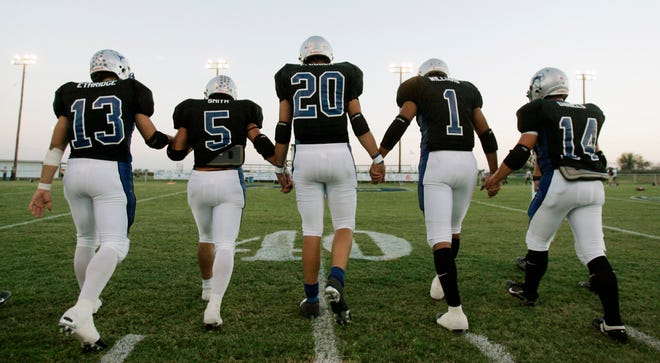 Richland Springs quarterback Tyler Ethridge (13) and teammates head to midfield for the coin toss of their six-man football game in Richland Springs, Texas, Friday, Sept. 28, 2007.  (AP Photo/Eric Gay)