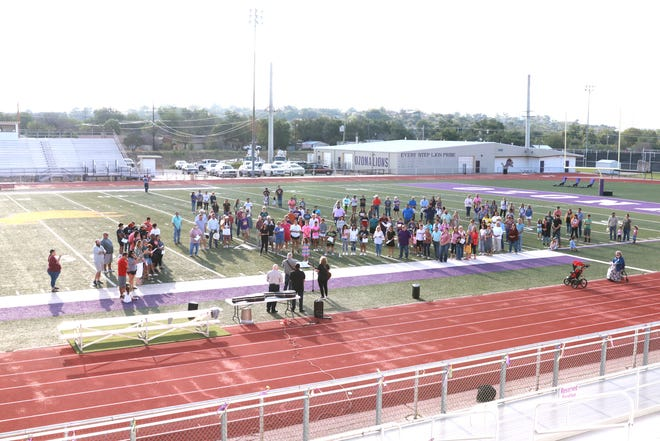Members of the community of Ozona, Texas, gather at Lions Stadium Sunday, Sept. 12, 2021, to pray for Jett, the infant son of the Ozona High School head football coach Jarryd Taylor and his wife Laura.