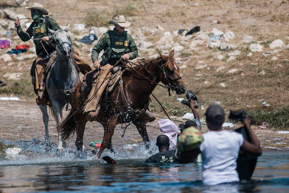 U.S. Customs and Border Protection officers attempt to contain migrants as they cross the Rio Grande into Del Rio, Texas, on Sept. 19, 2021.