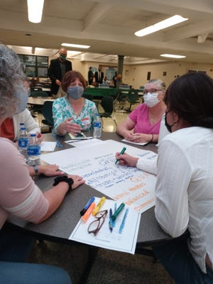 From left, Karon Lippincott of Sagamore Hills, Karen Byers of Sagamore Hills, Gina Picoult of Northfield Village, and Dawn Sedor of Sagamore Hills write down their responses to prompts given to them at Wednesday's forum on school facilities.
